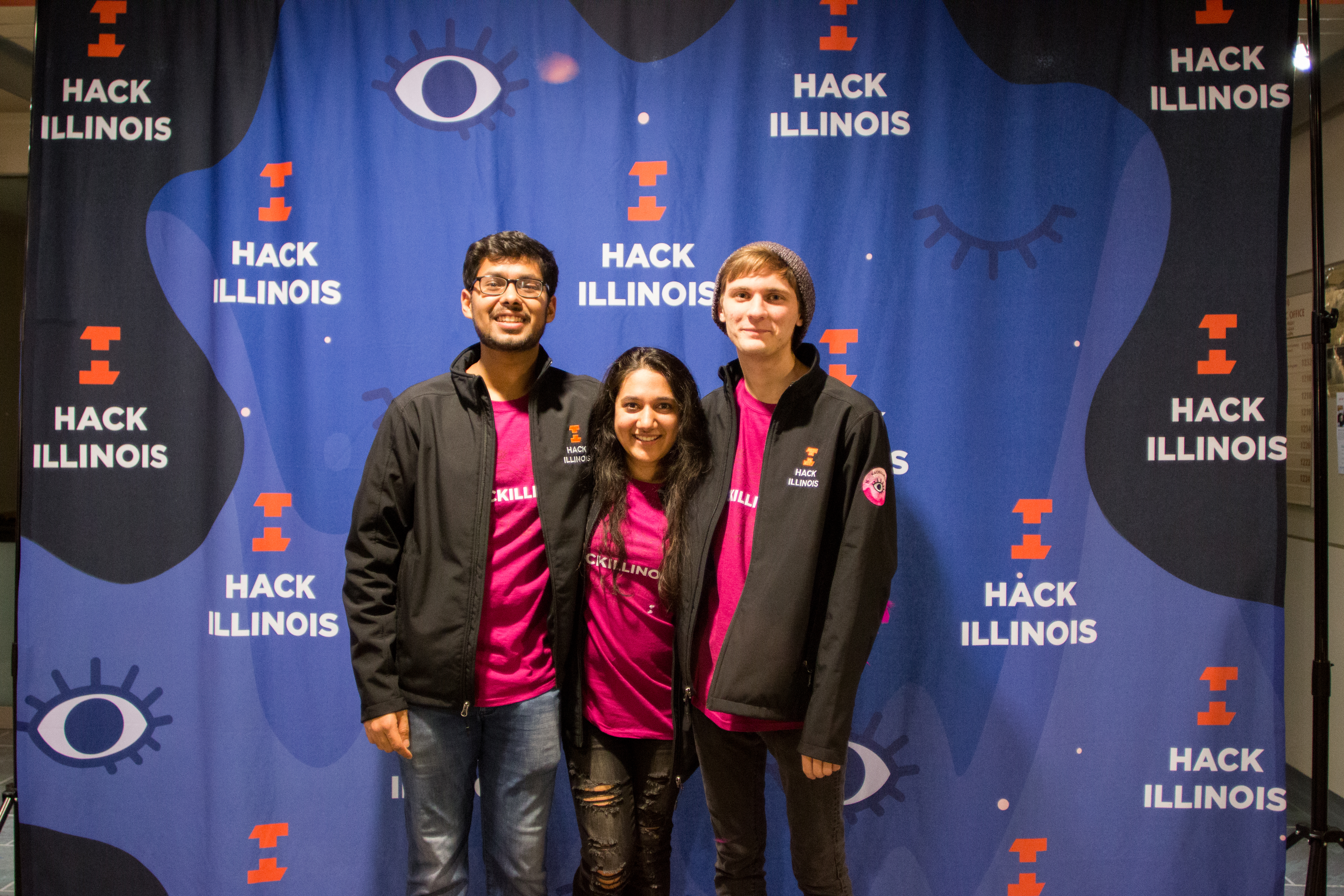 A group of HackIllinois 2018 staff members take a picture in front of the photobooth in their staff t-shirts and jackets.